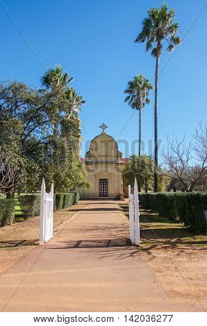NEW NORCIA,WA,AUSTRALIA-JULY 15,2016: Front of the Abbey Church of the Holy Trinity with palm trees and greenery under a blue sky in New Norcia, Western Australia.