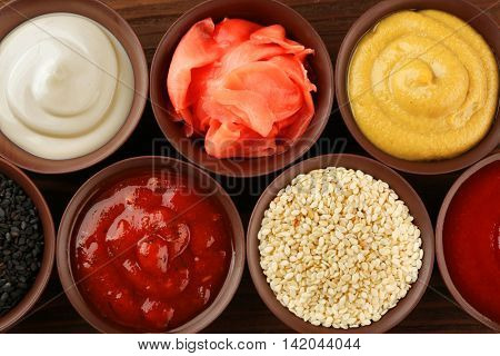 Fresh condiments and sauces on wooden background, closeup