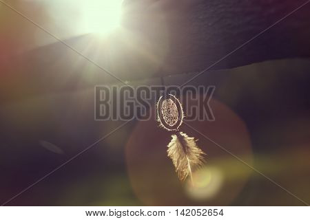 Handmade dreamcatcher hanging on a wooden fence in sunset of a beautiful sunny day