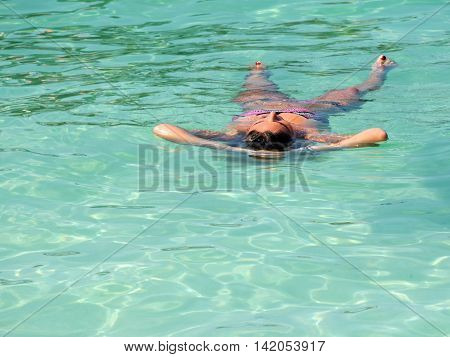 Young woman floating and relaxing in tropical crystal sea in summer. Relax and travel concept.