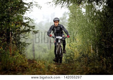 Revda Russia - July 31 2016: young man athlete cyclist rides through forest during Regional competitions on cross-country bike