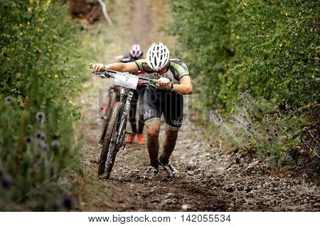 Revda Russia - July 31 2016: two men mountainbikers climb mountain on foot with their bicycle during Regional competitions on cross-country bike