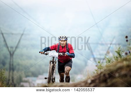 Revda Russia - July 31 2016: man mountainbiker climb mountain on foot with their bicycle during Regional competitions on cross-country bike