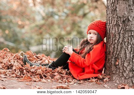 Stylish kid girl 3-4 year old wearing trendy winter jacket and knitted sitting under tree in park. Looking at camera. Posing outdoors. Childhood.