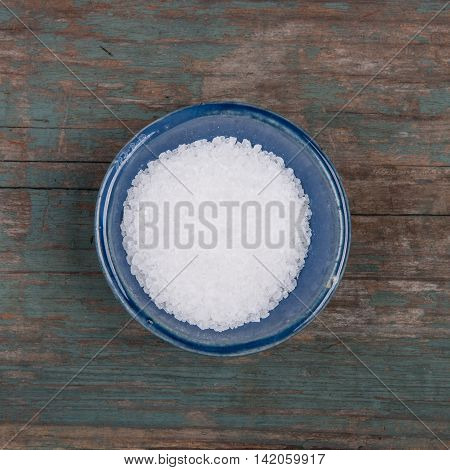 Small bowl of salt on a wooden table