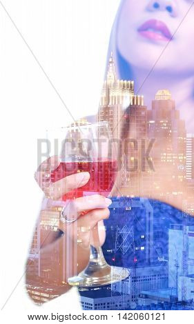 double exposure and de-focused woman hand in blue dress holding red wine in wineglass with midnight townscape background