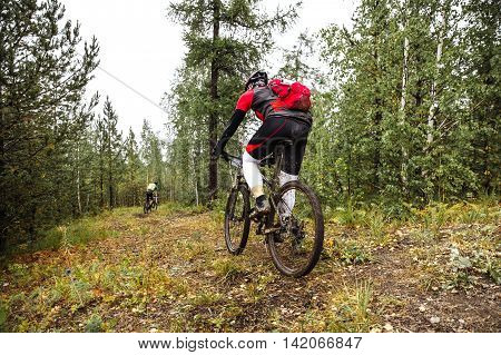male athlete riding through in forest on mountainbik behind backpack