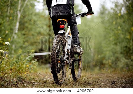 rear view of a dirty wheel bicycle and feet of athlete mountainbiker