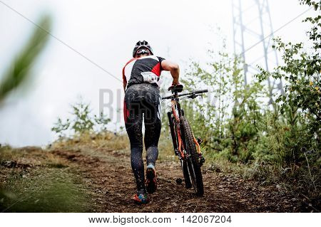 men mountainbikers climb mountain on foot with their bicycle during competitions in cross-country