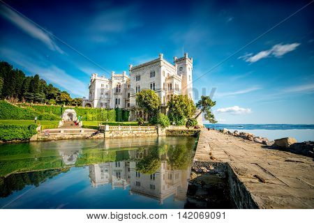 View on Miramare castle on the gulf of Trieste on northeastern Italy. Long exposure image technic with reflection on the water