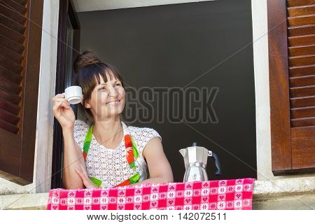 Portrait of young woman is enjoying a cup of freshly brewed coffee with Italian moka pot sitting near open window with traditional European wood brown shutters.