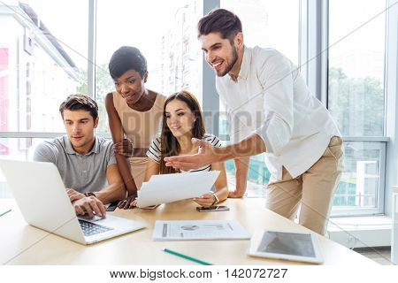Group of happy young business people using laptop and working together in office