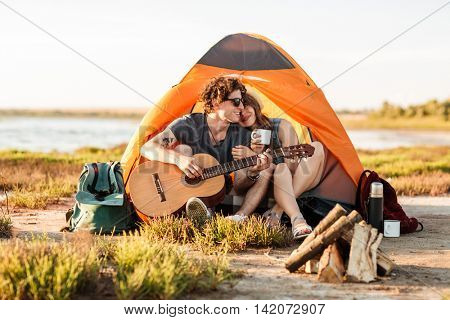 Portrait of a man playing guitar for his girlfriend camping at the beach