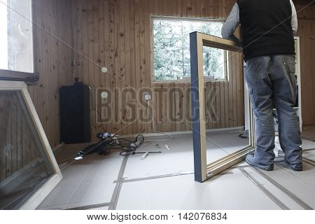 Worker preparing to install new three pane wooden windows in an old wooden house. Home renovation sustainable living energy efficiency concept.