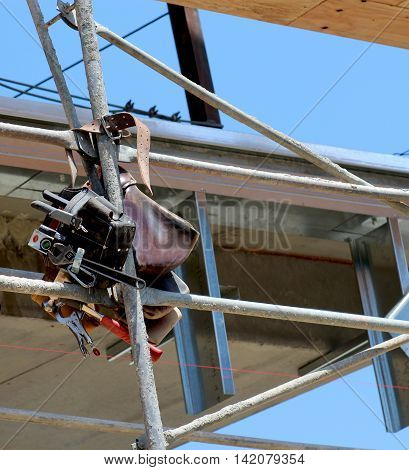 Construction worker's tool belt hanging from scaffolding on construction site filled with tools.