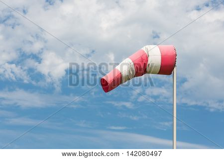 Windsock blowing in the wind against cloudy sky