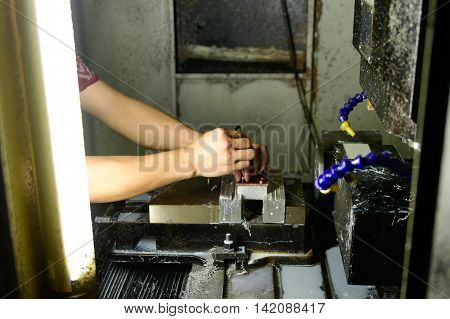 Factory worker setting up CNC milling machine
