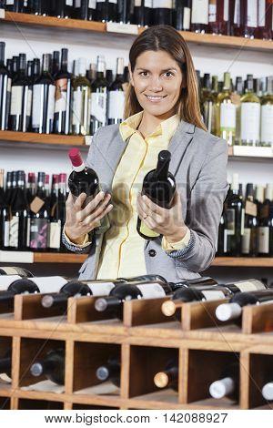 Woman Choosing Wine Bottles In Shop