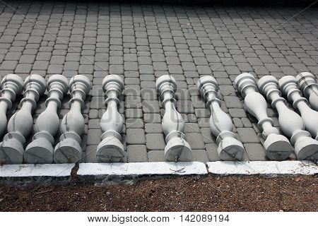 grey concrete balusters lying on sidewalk installation-ready