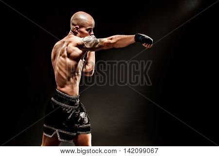 Muscular kickbox or muay thai fighter punching in darkness