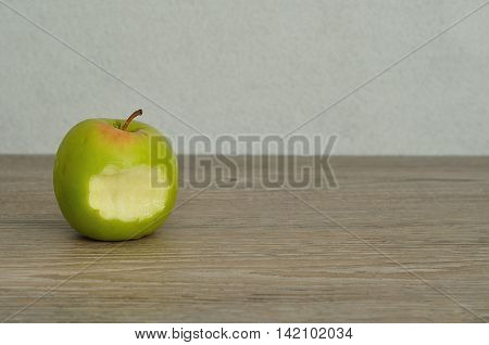A green apple with a bite taken out isolated on a white background