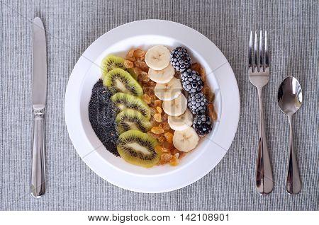 Kiwi banana dewberry raisin oatmeal smoothie bowl. Healthy eating breakfast.