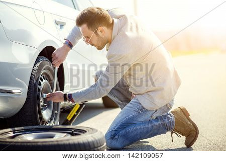 A young man with a silver car that broke down on the road.Changing tire on broken car on road.