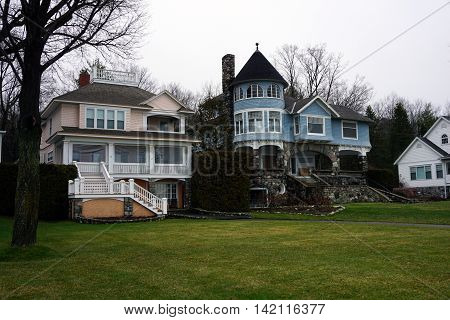 WEQUETONSING, MICHIGAN / UNITED STATES - DECEMBER 22, 2015: A pink mansion and a large blue mansion stand side by side on Beach Road in Wequetonsing.