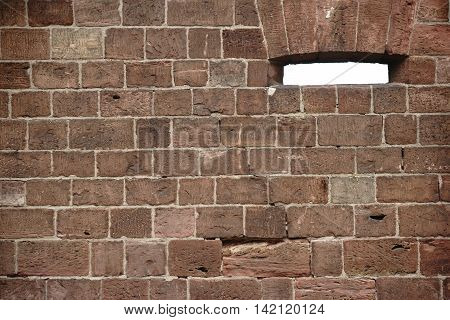 A wall of striking wine-red stones with a loophole or a window.
