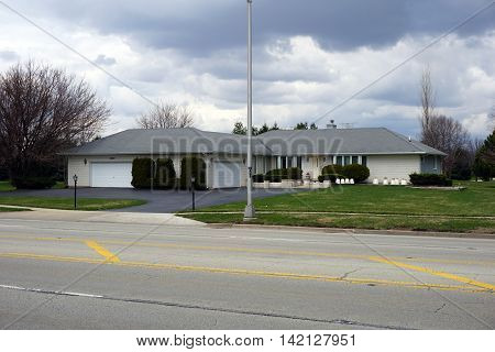 JOLIET, ILLINOIS / UNITED STATES - MARCH 19, 2016: A white brick ranch style home with an attached garage in Joliet.