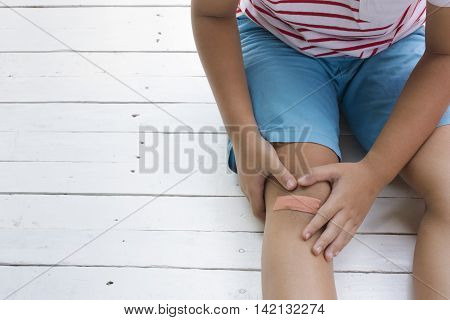 Child wound on knee and  on wooden white background,Top view and zoom in