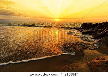 Ocean sunset sun rays is a colourful ocean scenic with sun beams bursting forth from the sun in a vivid surreal seascape.