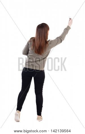 back view of writing beautiful woman. Rear view people collection.  backside view of person. Isolated over white background. A young girl in a gray sweater pulled up with a felt-tip pen in a hand.