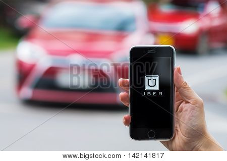 CHIANG MAITHAILAND - JUL 242016 : A MAN hand holding Uber app showing on iphone 6s on road and red car. Uber is smartphone app-based transportation network