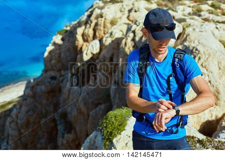male traveler with backpack standing on the trail on the cliff against sea and blue sky at early morning. Balos beach on background, Crete, Greece