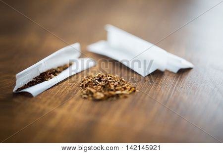 drug use, substance abuse, nicotine addiction and smoking concept - close up of marijuana or tobacco with cigarette paper