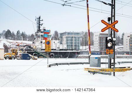 Railroad Crossing Near Port In Snowy Winter Day
