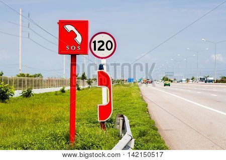 Emergency call box sits off to the side on highway.