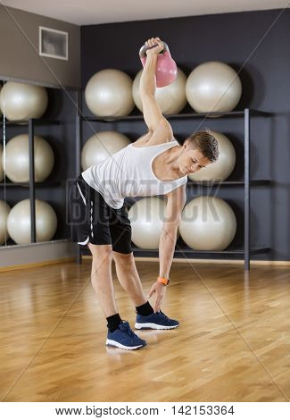 Man Exercising While Lifting Kettlebell On Floor At Gym
