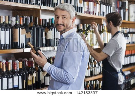 Customer Holding Wine Bottle While Salesman Working In Shop
