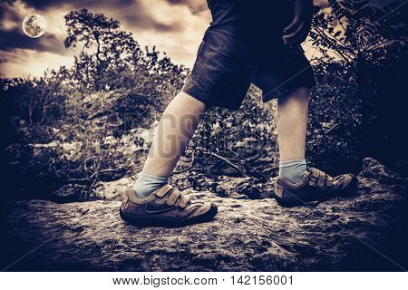 High contrast vintage portrait of boy's feet on the rock in the forest. Child wearing leather shoes and walking outdoor at dusk health concept. Bright full moon on sky.