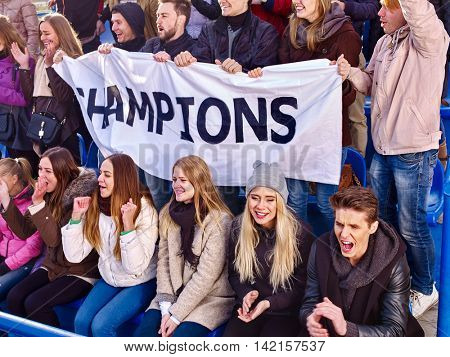 Sport fans holding champion banner and singing on tribunes. Group people.