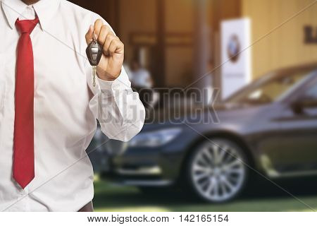 Car Salesman Handing Over The Keys For A New Car On Background