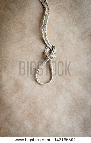 concept hangman's knot on kraft paper backgroun close up soft light top view