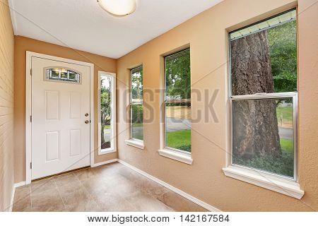 Empty Entryway With Tile Floor And White Front Door.