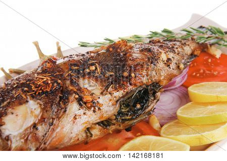 served main course: whole fried seabass served on plate with lemons,tomatoes and peppers