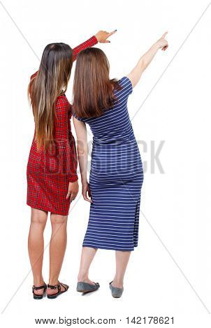 Back view of two pointing young girl. Rear view people collection.  backside view of person. beautiful woman friends  showing gesture. Rear view. Isolated over white background. Two girls in dresses