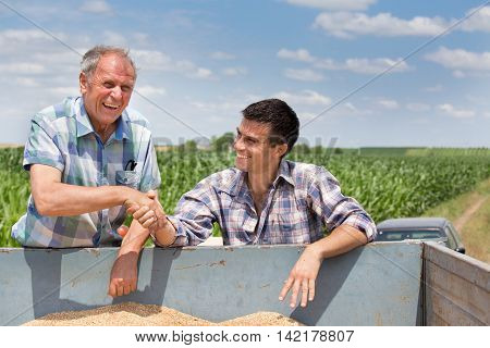 Farmers Shakig Hands On Pile Of Grains