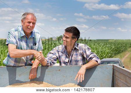 Farmers Shakig Hands On Pile Of Grains