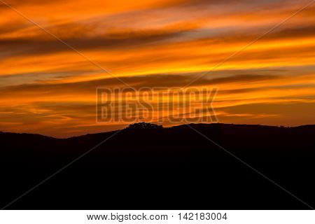 Village Of Sant' Antonino In Corsica Silhoutted Against Orange Evening Sky